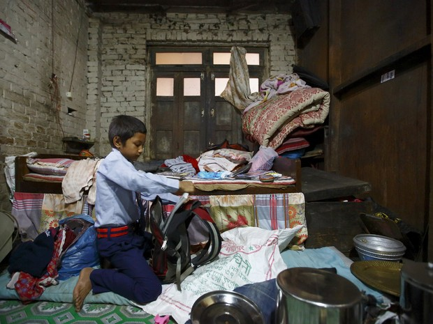 Niraj Ranjitkar, de 10 anos, prepara a mochila para voltar às aulas em Bhaktapur após terremotos (Foto: Reuters/Navesh Chitrakar)