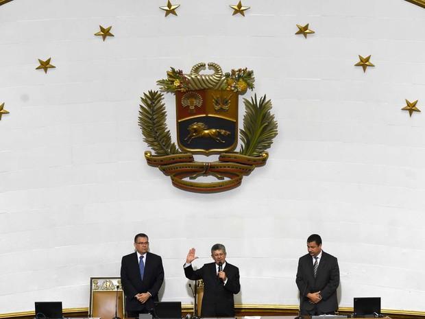 Novo presidente da Assembleia Nacional Henry Ramos Allup presta juramento ao lado do vice-presidente Enrique Márquez (esquerda) e do segundo vice-presidente Simón Calzadilla (direita) (Foto: AFP PHOTO/JUAN BARRETO)