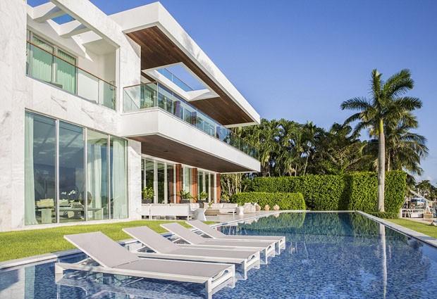 O jardim e a área da piscina seguem o mesmo estilo minimalista que se espalha pelo imóvel (Foto: Reprodução)