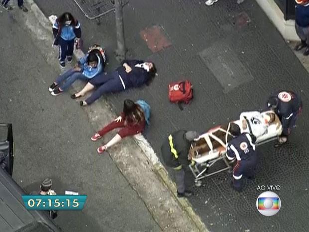 Passageiros são atendidos na calçada após acidente com van escolar em SP (Foto: Reprodução/TV Globo)