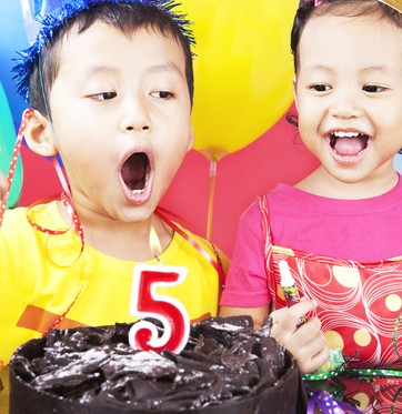 Criança assoprando vela de bolo de aniversário (Foto: Shutterstock)