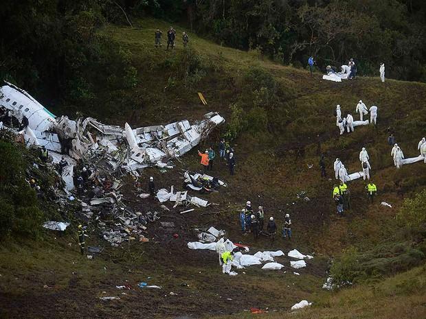 Equipes de resgate leva corpos embalados após retirá-los dentre os destroços do avião da LaMia perto de Medellín, na Colômbia (Foto: Raul Arboleda/AFP)