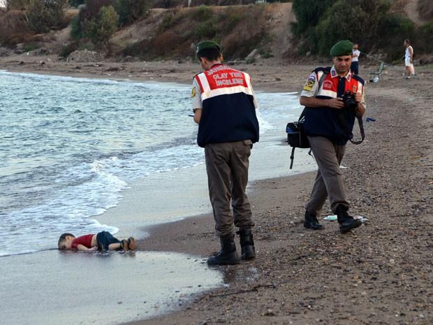 Agentes analisam local onde foi encontrado um menino morto em praia de Borum, na Turquia (Foto: AP/)