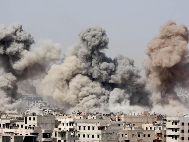 Fumaça sobe ao céu após bombardeios no subúrbio de Ghouta em Damasco, na Síria, no domingo (8). Segundo ativistas, os ataques partiram de forças leais ao presidente Bashar al-Assad (Foto: Diaa Al-Din/Reuters)