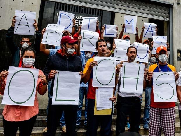 Opositores venezuelanos em greve de fome protestam em frente à Embaixada do Brasil em Caracas; grupo exibe frase 'Dilma, abra os olhos' (Foto: AFP PHOTO / FEDERICO PARRA)