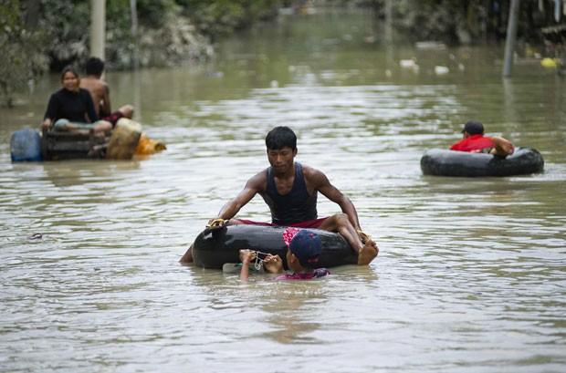 Residentes de áreas afetadas por enchentes em Kalay, no norte de Myanmar, usam boias para se locomover nas ruas alagadas nesta segunda-feira (3) (Foto: Ye Aung Thu/AFP)