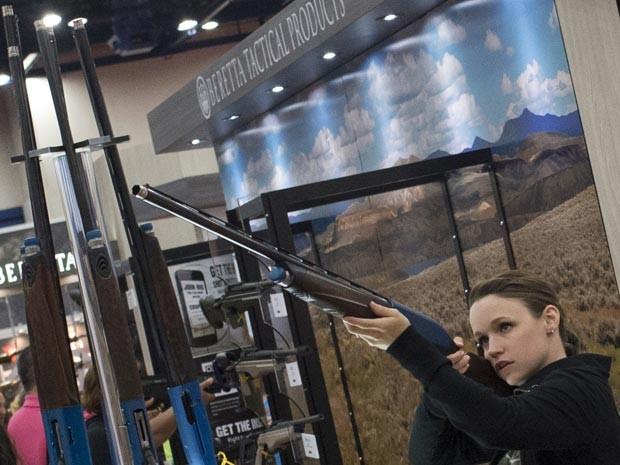 Mulher segura em rifle durante encontro da NRA (Foto: Reuters)