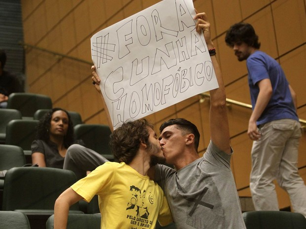 Manifestantes de grupos anti-homofobia se beijam e erguem cartaz durante protesto contra o presidente da Câmara dos Deputados, Eduardo Cunha (PMDB) (Foto: Hélvio Romero/Estadão Conteúdo)
