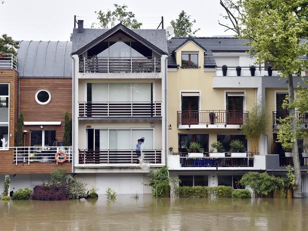 Um homem esvazia um balde de água de sua casa, neste sábado (4), em Neuilly-sur-Seine, perto de Paris (Foto: ALAIN JOCARD/AFP)