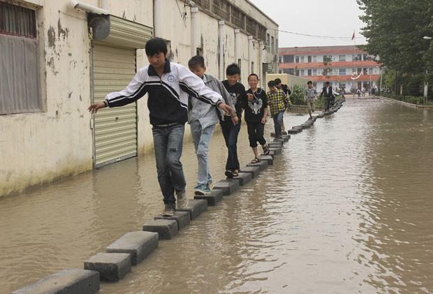 Alunos usam um caminho improvisado com blocos de concreto para atravessar uma via que há anos permanece alagada em Shangqiu (Foto: Stringer/Reuters)