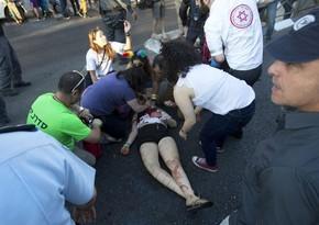Paramédicos atendem pessoa atacada com faca durante a Parada Gay de Jerusalém nesta quinta-feira (30) (Foto: Sebastian Scheiner/AP)