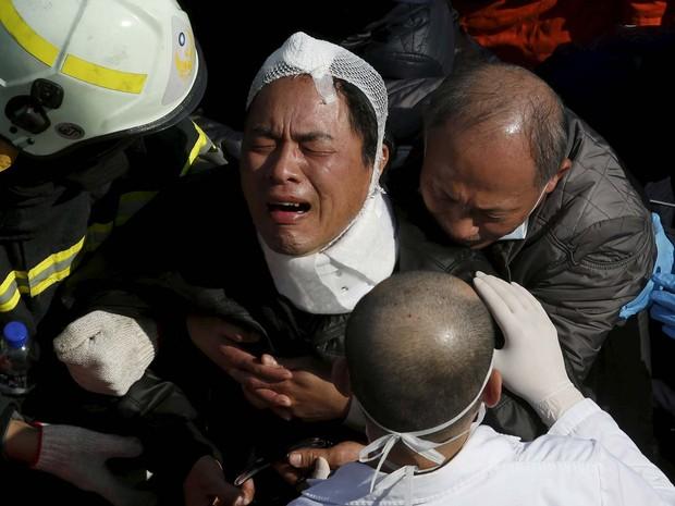 Homem chora após receber a notícia de um de seus faniliares morreu após a queda de prédio de 17 andares como terremoto em Taiwan (Foto: REUTERS/Tyrone Siu)