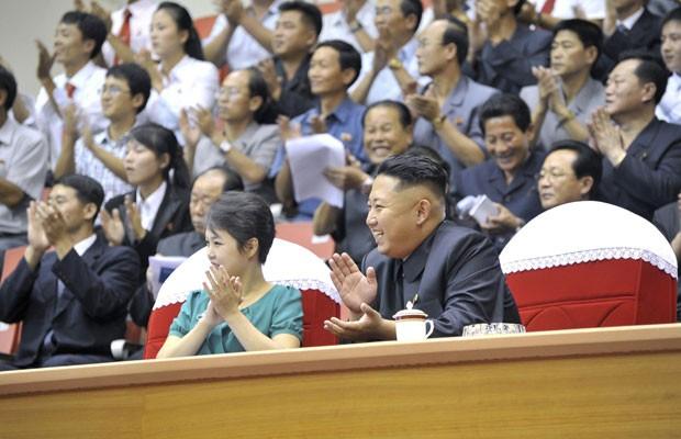 O líder norte-coreano, Kim Jong-un (direita), sorri ao lado da esposa, Ri Sol-ju, ao assistirem à apresentação de levantamento de peso em Pyongyang, neste domingo (15) (Foto: Reuters)