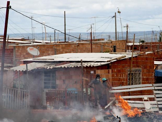 Manifestantes colocam fogo em madeira durante protesto contra derrubada de casas no Sol Nascente, no DF (Foto: Vianey Bentes/TV Globo)