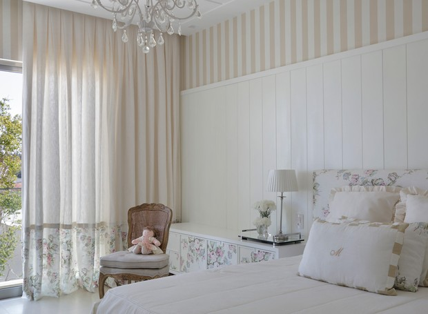 Com a premissa de ter um ar romântico, o quarto da filha ganhou papel de parede floral. Ele também foi usado para revestir o criado-mudo desenhado por Babi. Cortina da Micasa Atelier  (Foto: Denílson Machado - MCA Estúdio/Divulgação )
