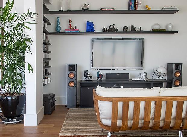 Na pequena sala de TV, prateleiras acomodam alguns livros e objetos decorativos (Foto: Divulgação)