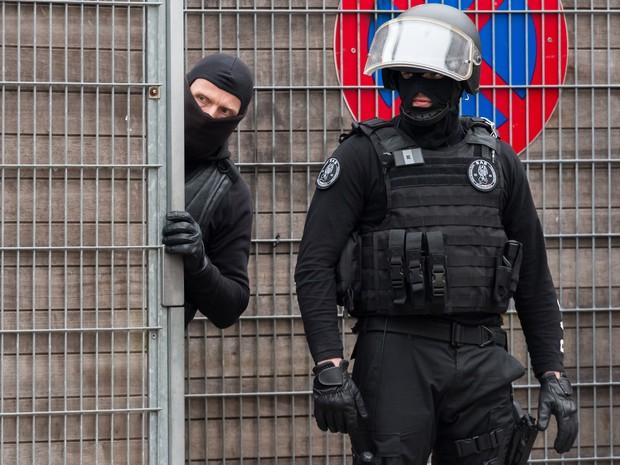 Policiais vigiam a entrada de uma escola durante operação de busca a terroristas no bairro de Molenbeek, em Bruxelas  (Foto: Geert Vanden Wijngaert/AP)
