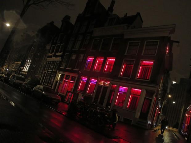 Homem caminha por um edifício com janelas de luz vermelha onde as prostitutas trabalhem nas ruas de Amsterdã. (Foto: Alexander Klein/AFP)