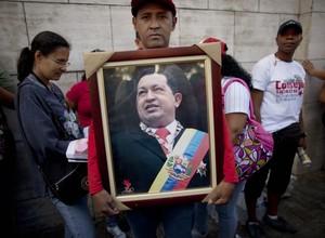 Apoiador de Chávez segurou uma foto do presidente durante a eleição da Assembleia Nacional, no sábado (5) (Foto: AP Photo / Ariana Cubillos)
