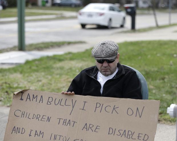 Cartaz destacava que Aviv fazia bullying contra crianças com deficiência  (Foto: Tony Dejak/AP)