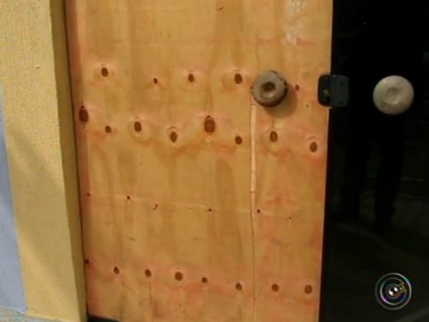 Tapume está na porta para improvisar o vidro que está quebrado (Foto: Reprodução / TV TEM)