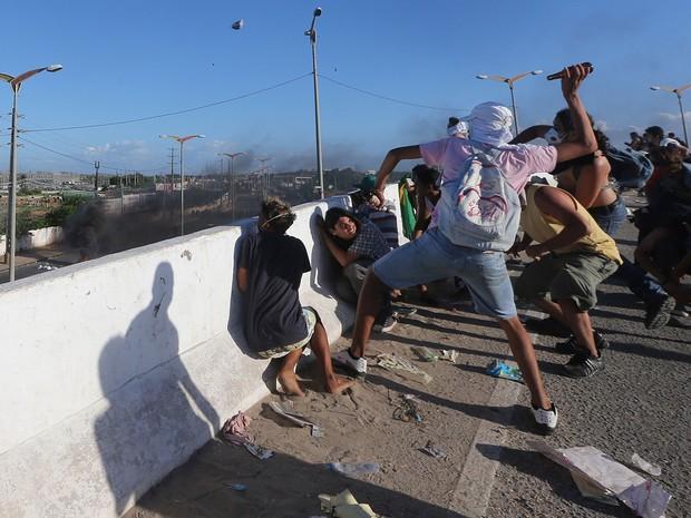 Manifestantes e policiais militares entram em novo conflito na tarde desta quarta-feira (19), na Avenida Paulino Rocha, bem próximo à Arena Castelão (Foto: Andre Penner/AP)