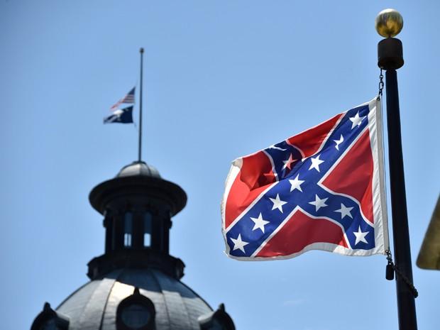 Em foto de 19 de junho, as bandeiras dos EUA e da Carolina do Sul são vistas a meio mastro, enquanto a bandeira confederada continua hasteada normalmente em frente ao prédio do governo estadual (Foto: AFP Photo/Mladen Antonov)