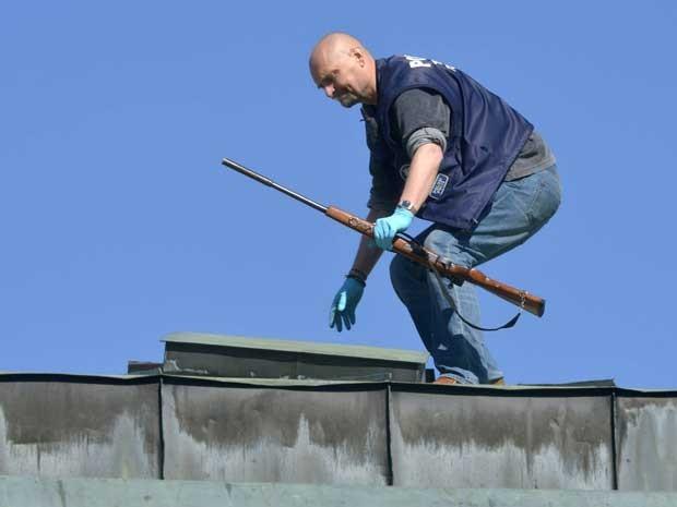 Um policial recupera num telhado a arma do atirador. (Foto: Lehtikuva / Jussi Nukari / AP Photo)
