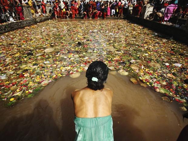Uma devota se prepara para mergulhar em um rio na cidade de Katmandu, no Nepal, na celebração do Matathirtha, o Dia das Mães.  (Foto: Navesh Chitrakar/Reuters)