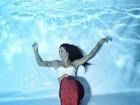 Amanda Djehdian posa de top e com cauda de sereia