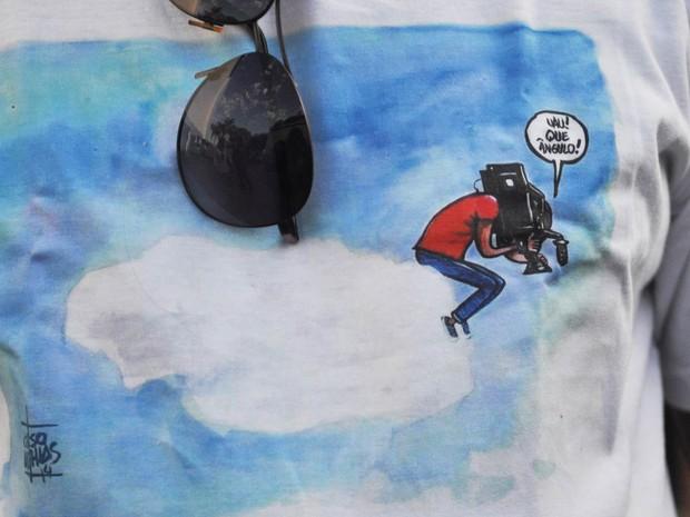 Colegas do cinegrafista Santiago Andrade, funcionários da Rede Bandeirantes usam camiseta com homenagem ao colega morto, durante o velório no cemitério do Caju, no Rio de Janeiro. Santiago é retratado sobre uma nuvem, filmando a Terra. (Foto: Armando Paiva/Fotoarena/Estadão Conteúdo)