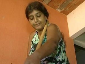 Moradora precisa apoiar cabo da vassoura do braço para varrer a casa (Foto: Reprodução/TV Gazeta)