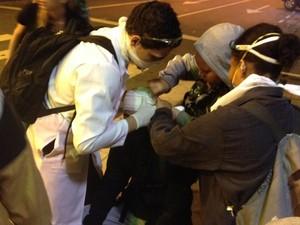 Médico e voluntários prestam socorro a manifestante atingido por bala de borracha na cabeça (Foto: Gabriel Barreira/G1)