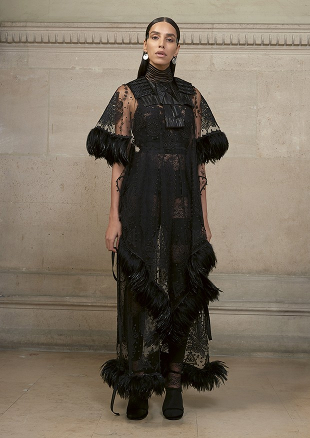 Lea T wears an embroidered illusion-tulle dress with delicate geometric floral motifs, trimmed with ribbons of black rooster feathers. At the chest is a cut-and-glued feathered front worn with an encrusted-lace jersey jumpsuit (Foto: Givenchy)