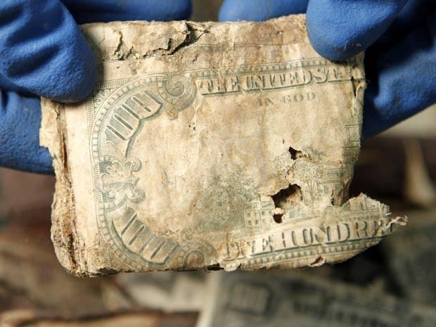Eric Walsh, funcionário do Departamento do Tesouro dos EUA, mostra notas danificadas de US$ 100 durante feira mundial sobre dinheiro em Boston, nos EUA. Segundo o órgão, as notas foram danificadas pela água depois que foram enterradas em uma mochila em ce (Foto: Steven Senne/AP)
