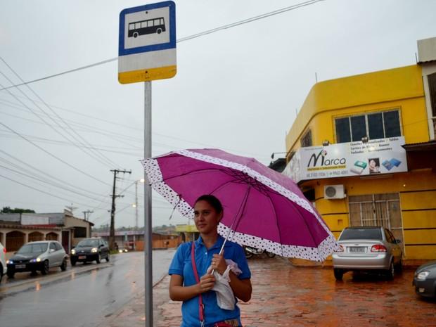 Durante chuva, jovem esperou por ônibus em parada sem cobertura no bairro Floresta, em Rio Branco (Foto: Quésia Melo/G1)