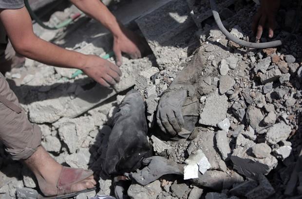 Durante trégua de 12 horas na Faixa de Gaza neste sábado (26), palestinos tentam resgatar corpo dos escombros de uma casa destruída (Foto: AP Photo/Khalil Hamra)