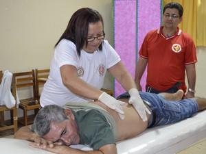 Morador recebendo serviço de massagem em ação (Foto: Graziela Miranda/ G1 Amapá)