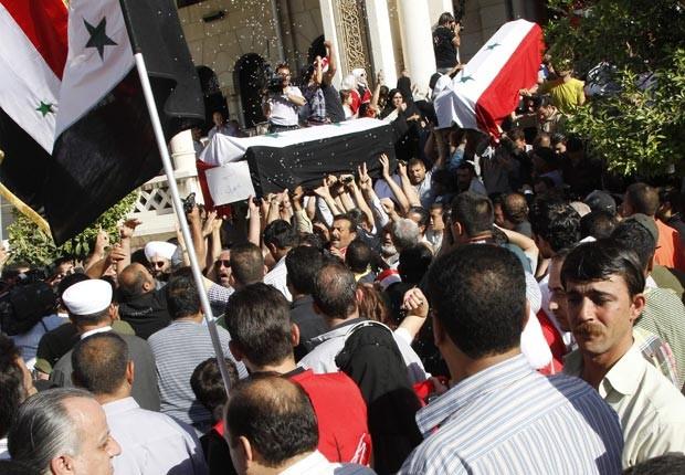 Caixões com corpos de vítimas dos atentados da quarta-feira são carregados próximo a mesquita em Damasco, neste sábado (12) (Foto: Reuters)