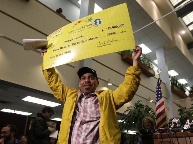Pedro Quezada, o vencedor do prêmio principal da Powerball, segura o cheque promocional durante uma coletiva de imprensa na lotérica de Nova Jersey (Foto: AP Photo / Julio Cortez))