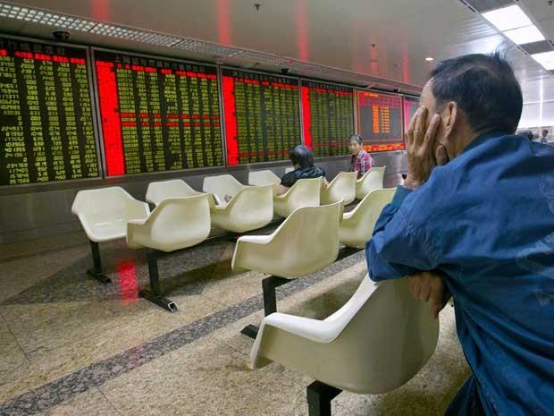 Chinês monitora preços de ações em uma corretora em Pequim, na China (Foto: Mark Schiefelbein / AP Photo)