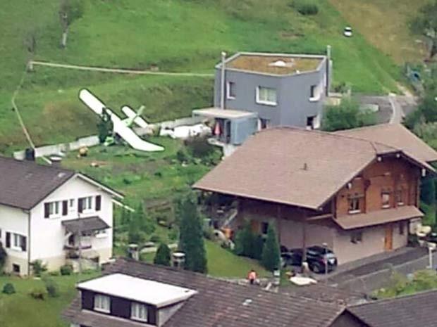Um dos aviões que colidiram durante show aéreo neste domingo (23) é visto em meio ao vilarejo de Dittingen, na Suíça (Foto: REUTERS/Kantonspolizei Basel Landschaft/Handout via Reuters)