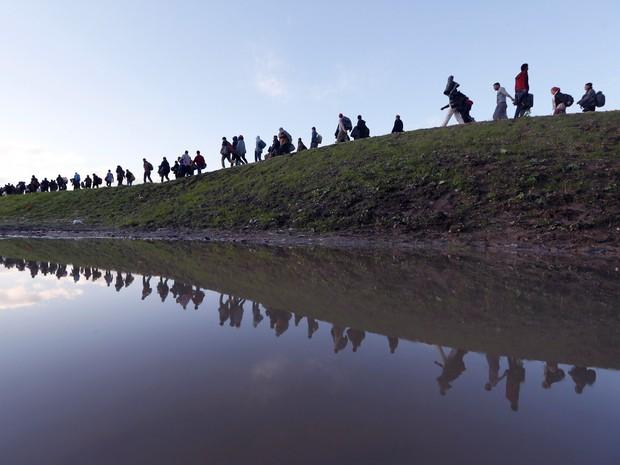 Migrantes caminham a pé nos arredores de Brezice, na Eslovênia. O Ministério do Interior do país levantou a possibilidade da criação de barreiras físicas ao longo de sua fronteira sudeste se o número de migrantes e refugiados aumentado (Foto: Srdjan Zivulovic/Reuters)
