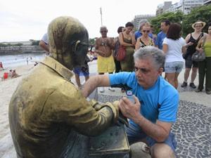 Voluntário limpa estátua de Drummond. (Foto: Maíra Coelho/Agência O Dia/Estadão Conteúdo)