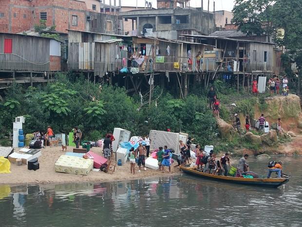 Famílias utilizam canoa para tentar salvar pertences de incêndio, em Manaus (Foto: Adneison Severiano/G1 AM)