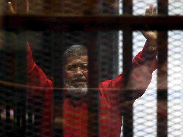 O ex-presidente egípcio Mohamed Mursi cumprimenta seus advogados por trás das grades em uma corte no Cairo, em 21 de junho de 2015 (Foto: Reuters/Amr Abdallah Dalsh/File Photo)