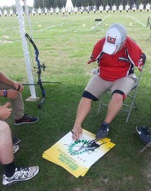 Matt dá atenação a fãs e autografa cartaz com o pé (Foto: Reprodução/Facebook) height=380
