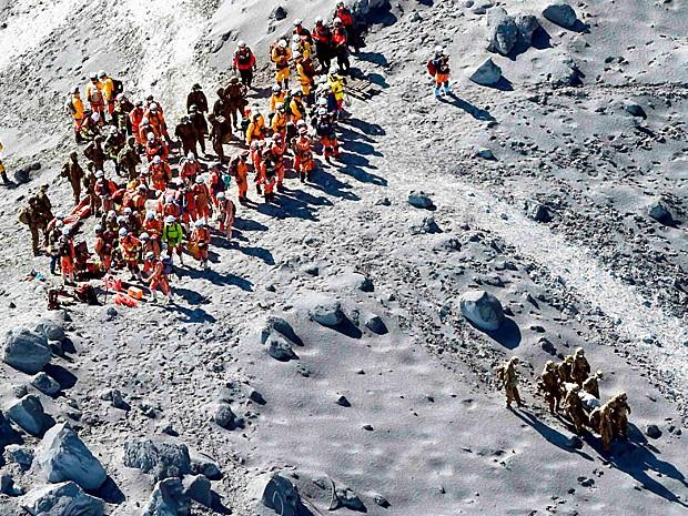 Equipes de resgate durante operação de retirada de vítimas do vulcão no Japão (Foto: Kyodo/Reuters)