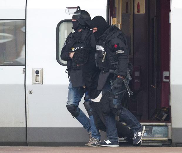 Policiais da divisão antiterrorismo holandesa carregam homem detido após se trancar no banheiro de um trem em Roterdã nesta sexta-feira (18)              (Foto: Peter Dejong/AP)