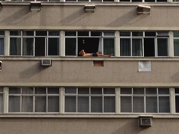 Homem toma sol na janela do 10° andar de um prédio em Copacabana (Foto: Daniel Nassar / Arquivo pessoal)